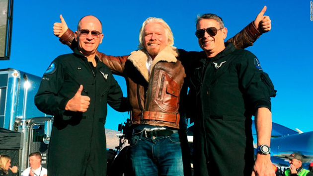 "Richard Branson celebrates with pilots, Rick ""CJ"" Sturckow (left), and Mark ""Forger"" Stucky (right), after Virgin Galactic's tourism spaceship climbed more than 50 miles high. (Source: CNN)"