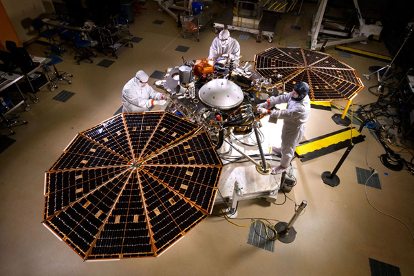 Scientists work on the real-life contents of InSight, including its solar-panel arrays. (Source: NASA/JPL-Caltech/Lockheed Martin)