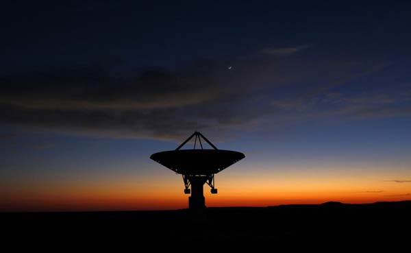 Dawn breaks over a radio telescope dish of the KAT-7 Array pointing skyward at the proposed South African site for the Square kilometer Array (SKA) telescope near Carnarvon in the Northern Cape province. This picture was taken on May 18, 2012. (Source: Reuters/Independent)