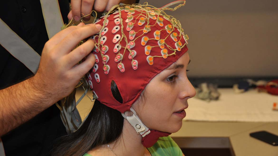 Ashley Livingstone, an SFU first year master's student, models a cap that is fitted with 128 electrodes. They are hooked up to monitor the wearer's brain activity.