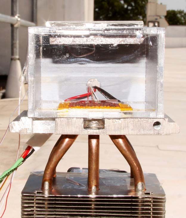 The harvester sitting atop a roof at MIT. The MOF is just below the glass plate on top, which lets sunlight in to heat the MOF and drive off the absorbed water. The yellow and red condenser sitting at the bottom is covered with water droplets. MIT photo by Hyunho Kim.