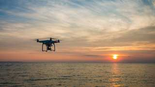 Black Quadcopter Drone Flying on the Sea Shore Under Blue and White Sky during Sun Set