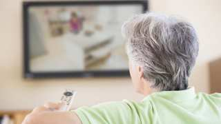 Man watching television using remote control: Source Stock Image