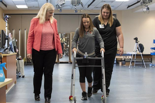 Seen in this picture is one of the volunteers of the study, Kelly Thomas, walking with support. After a horrible road accident, a few years ago, she sustained a spinal cord injury and was left paralyzed. On her left is Susan Harkema of the Kentucky Spinal Cord Injury Research Center. (Source: University of Louisville in Kentucky)